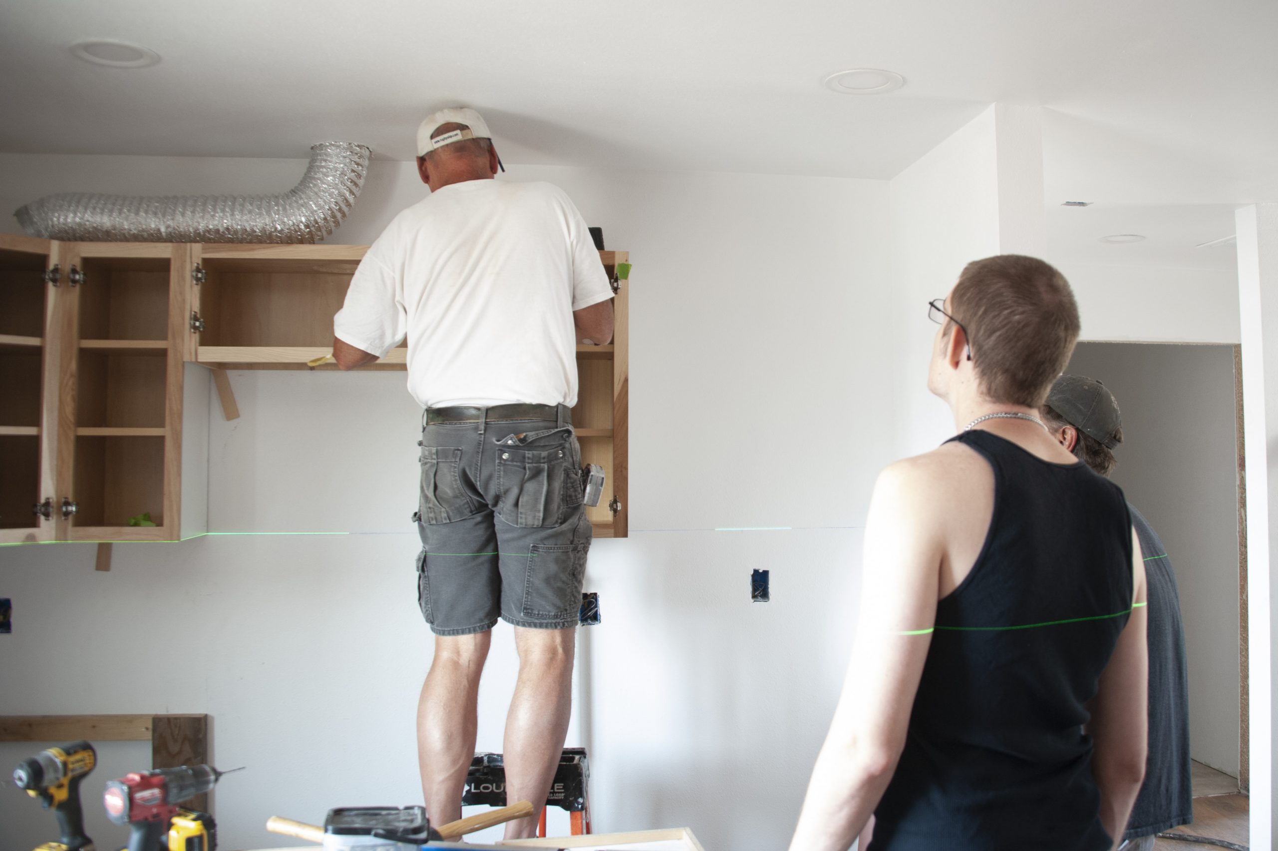 Kelcey Leaseburg and Bob Behal Workling on Kitchen Cabinets